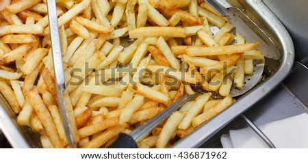 French fries fresh cooked. Restaurant deep fryer, metal container with lots of potatoes fried. Street food, fast food. Potato fries closeup. Roasted tasty potatoes - stock photo
