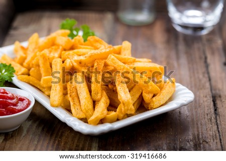 French fries in a bowl on a wooden background - stock photo