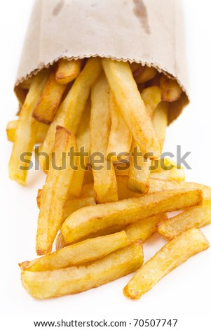 French fries in a small brown paper bag. Shallow depth of field. - stock photo