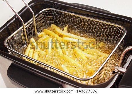 French fries in hot fat in a deep fryer - stock photo