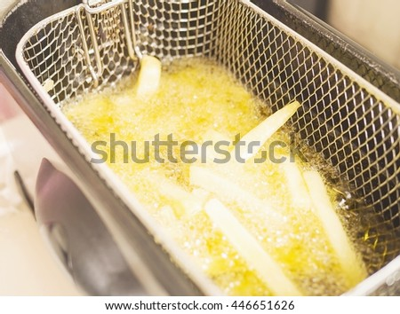 French fries in hot oil pan - stock photo