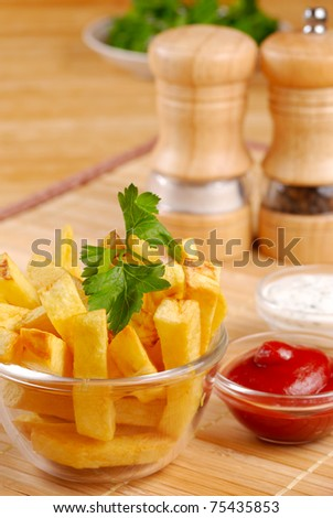 French fries in the glass bowl on the wooden table - stock photo