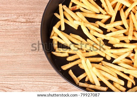French fries in the pan on a wooden background