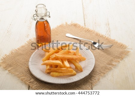 french fries on a white paper plate and malt vinegar