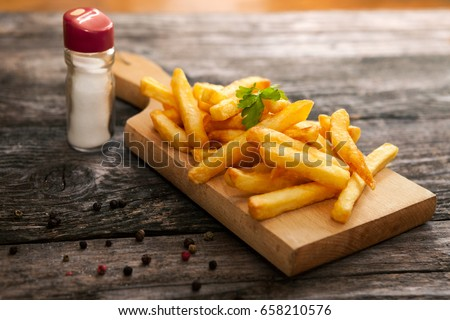 French fries on cutting board with bottle of salt