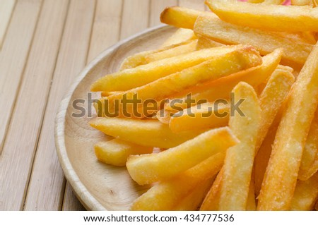 French fries sprinkled salt on wood plate - stock photo