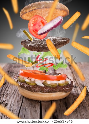 French fries with burger in freeze motion isolated on white - stock photo
