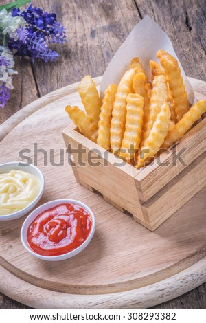 French fries with ketchup and mayonnaise on wooden background