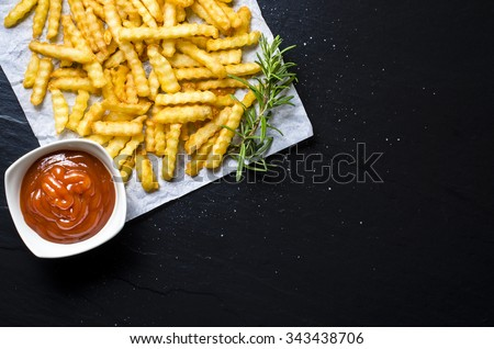 French fries with ketchup over dark table. Top view - stock photo