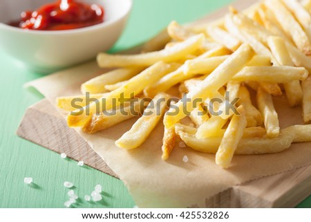 french fries with ketchup over green background - stock photo