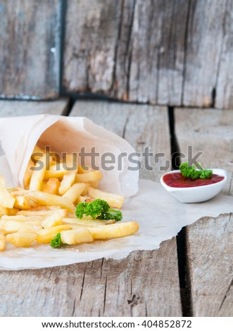 French fries with sauce on a wooden background