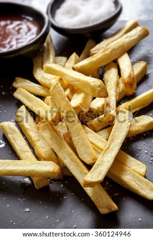 French fries with sea salt and ketchup, on black slate.  Side view. - stock photo