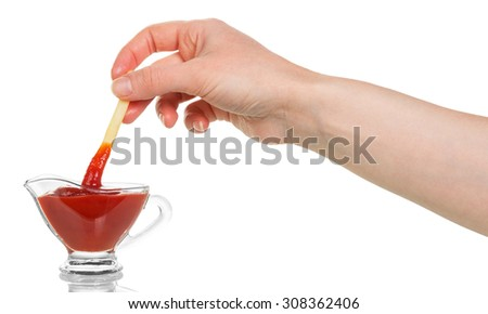 French fry being dipped in ketchup over white background - stock photo