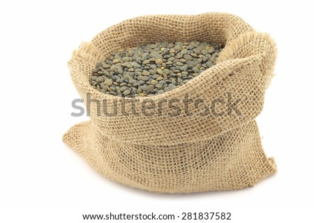 French green lentils (lentilles du Puy) in a burlap bag on a white background - stock photo