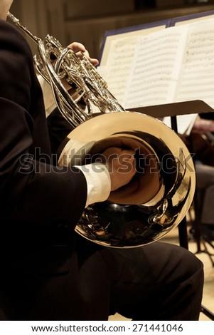 French horn in the hands of the musician - stock photo