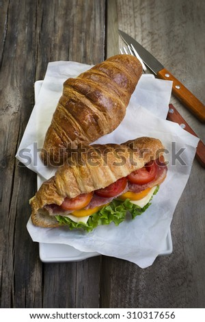 French loaf Cheese and ham sandwich on rustic wooden table top. Close-up image. - stock photo