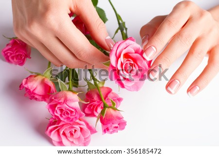 French lunar manicure with bouquet of pink roses close-up. Beautiful female nails.