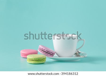 French macarons and coffee cup on aquamarine background - stock photo