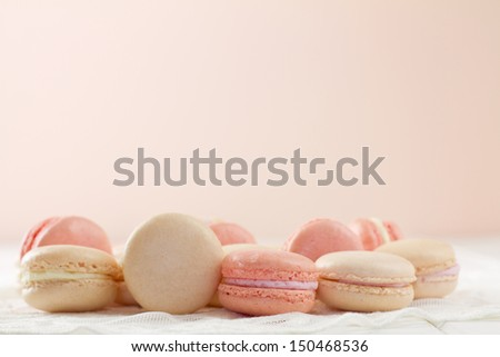 French macarons on white wood table with lace over Soft pink and white hues with copy space. A fresh, feminine image. - stock photo