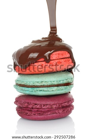 French macaroons are drizzled with melted chocolate on white background - stock photo
