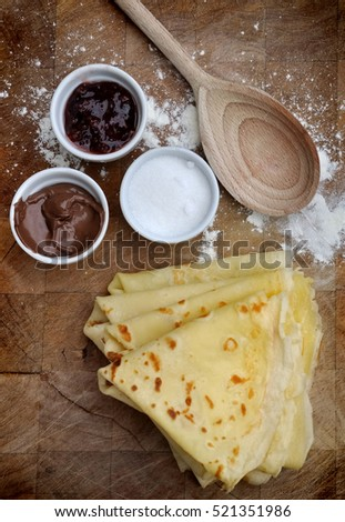 french pancakes homemade with sugar on wooden plank