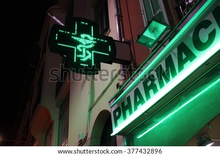 French Pharmacy Neon Green Sign by Night. Bowl of Hygieia is one of the symbols of Pharmacy