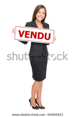 French real estate agent holding french sold sign - agent immobilier avec pancarte vendu. - stock photo