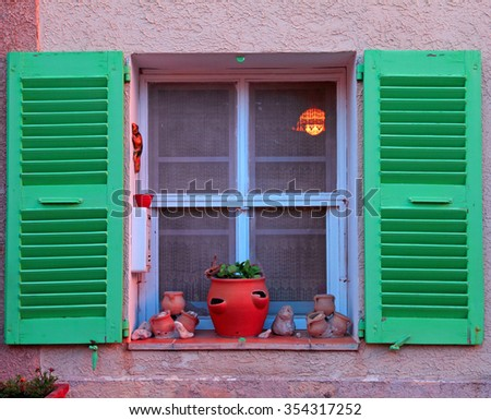 French rustic window with green wood shutters and flower pot in stone rural house, Provence, France. Sunset light - stock photo