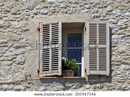 french rustic window with old wood shutters in stone rural house, Provence, France. - stock photo