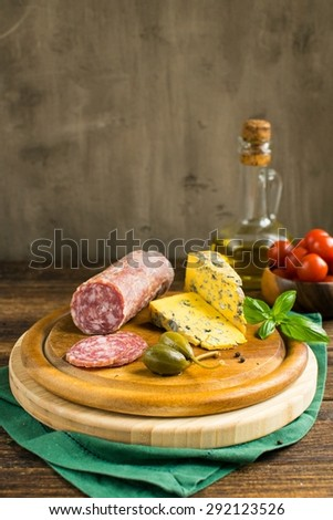 french snacks on a cutting board on a brown, wooden table