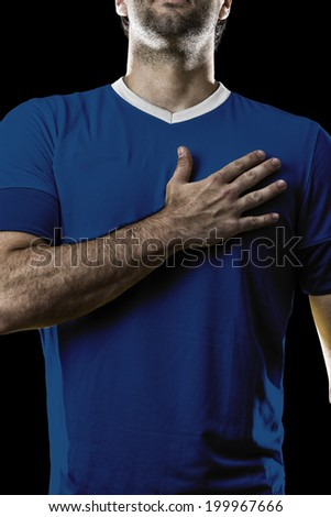 French soccer player, listening to the national anthem with his hand on his chest. On a black background. - stock photo