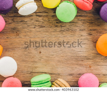 french sweet delicacy, colourful macaroons variety with wood Background,vintage tone. - stock photo