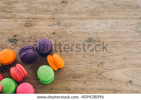 french sweet delicacy, colourful macaroons variety with wood Background,vintage tone - stock photo
