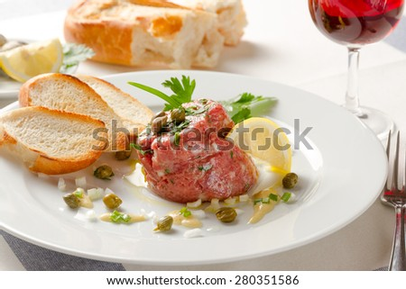 French tartar with fresh juicy meat from young bull served with mustard sauce, capers, french baked baguette and a glass of fine red wine - stock photo