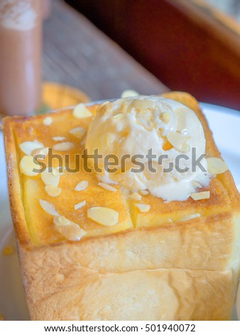 French toast (or honey toast), Consists of bread topped with vanilla ice-cream, almonds and honey. Serve with butter and honey. Selective focus.