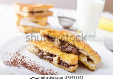 French toast stuffed with chocolate and banana, fresh milk, clean composition - stock photo