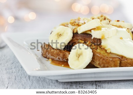 French toast topped with sliced bananas, nuts, cream cheese sauce and caramel syrup. Extreme shallow depth of field with selective focus on french toast and some blur on corner of plate. - stock photo