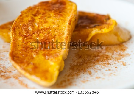 French toast with honey and sugar dressing on white plate