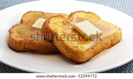 french toast with piece of butter on a white plate - stock photo