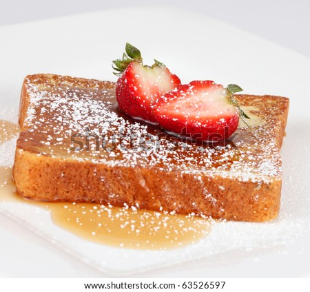French toast with powdered sugar and a strawberry on white - stock photo