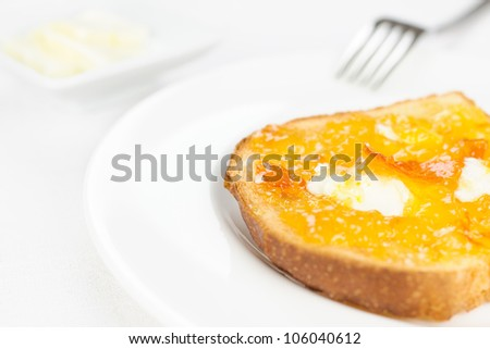French toast with spread bitter orange marmalade or jam with candied peel, butter curls, fork on background and dishware on white tablecloth
