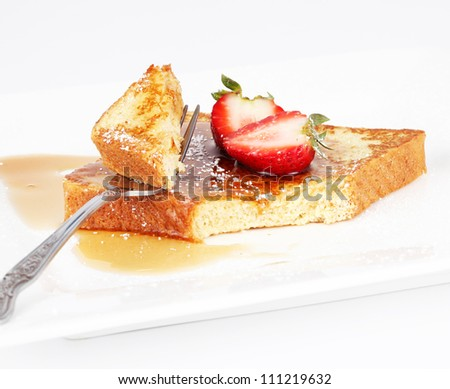 French toast with syrup and strawberry on a white plate. - stock photo