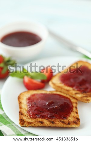French toasts with jam and strawberry on wooden table