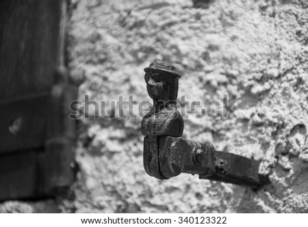 French traditional shutter catch for holding shutters open in the shape of a woman head. Aged photo. Black and white. - stock photo