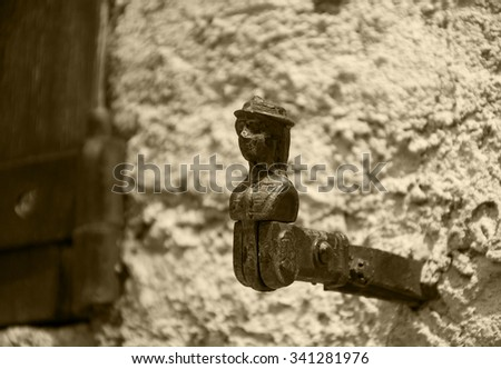 French traditional shutter catch for holding shutters open in the shape of a woman head. Aged photo. Sepia. - stock photo