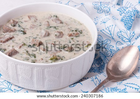 French veal ragout in white porcelain bowl on white provence-style napkin. Blanquette de veau. - stock photo
