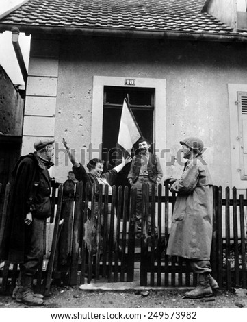 Frenchwoman exclaims to a neighbor and a U.S. soldier, 'Tout Belfort Est Libre,' Nov. 25, 1944. U.S. forces liberated much of northwestern France in the last months of 1944.