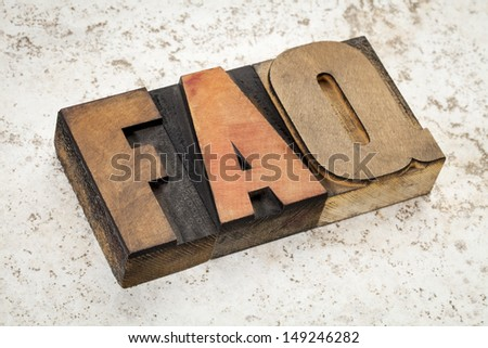 frequently asked questions - FAQ acronym - text in vintage letterpress wood type on a ceramic tile background - stock photo