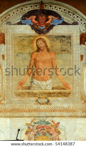 Fresco of Jesus Christ after the crucifixion in a baroque frame on the outside of a wall of a building in Italy - stock photo