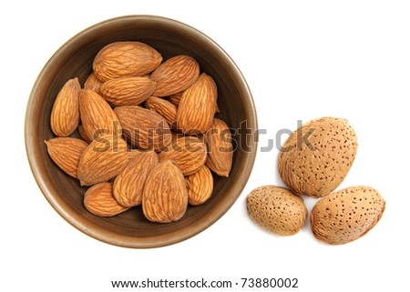 Fresh almonds in the clay bowl isolated on white - stock photo